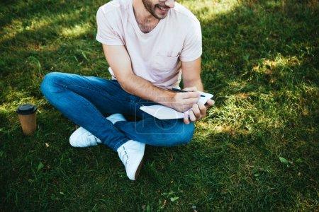 Foto de Recortar imagen de hombre sonriente haciendo notas sobre verde hierba en el Parque - Imagen libre de derechos