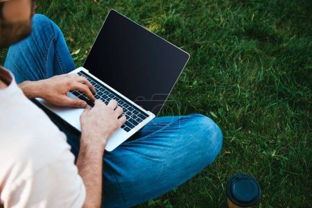 Photo for Cropped image of man using laptop with blank screen in park - Royalty Free Image