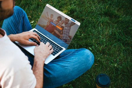 cropped image of man using laptop with couchsurfing website in park
