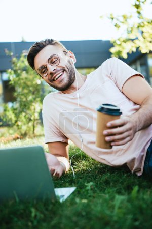 smiling handsome man taking part in webinar and lying on grass in park