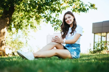 Photo for Smiling beautiful girl sitting on green grass in park and looking at camera - Royalty Free Image