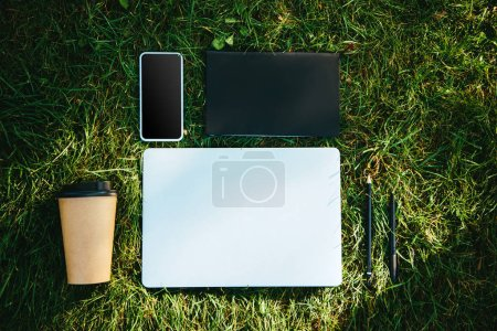elevated view of digital devices and disposable coffee cup on green grass in park