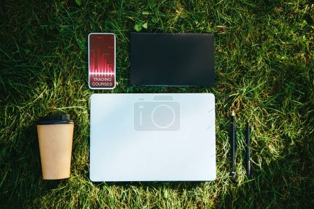 top view of smartphone with trading courses appliance and coffee in paper cup on green grass in park