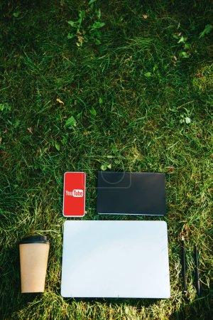 Foto de Vista superior del smartphone con la aplicación de youtube, portátil y café en la taza de papel sobre la hierba verde en el Parque - Imagen libre de derechos