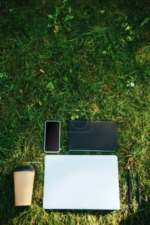 Photo for Elevated view of gadgets and coffee in paper cup on green grass in park - Royalty Free Image