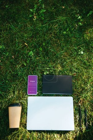 top view of smartphone with instagram appliance, laptop and coffee in paper cup on green grass in park