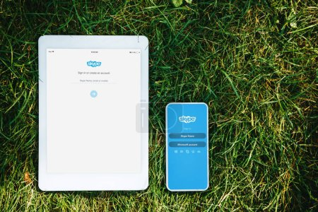 Photo for Elevated view of tablet and smartphone with loaded skype pages on green grass in park - Royalty Free Image