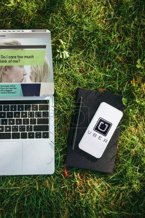 top view of laptop with website and smartphone with uber appliance on green grass in park