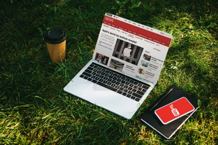 Photo for Laptop with bbc news and smartphone with youtube page on green grass in park - Royalty Free Image