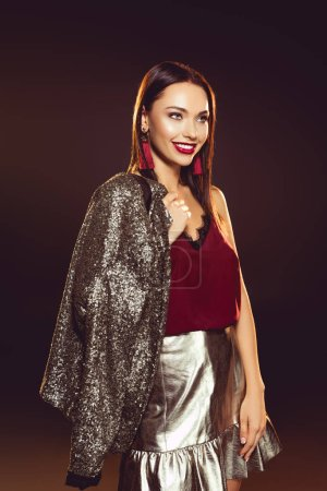 cheerful young woman in glamour dress posing with jacket over shoulder on black with backlit