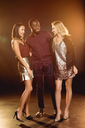 happy african american man hugging two attractive women on new year party