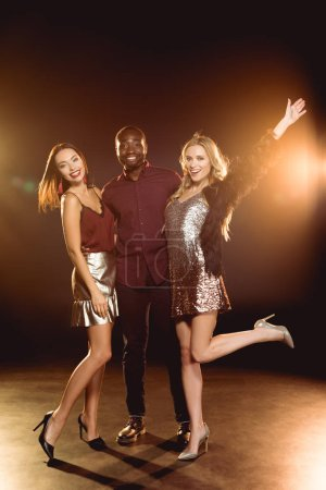 cheerful african american man hugging two attractive women on new year party