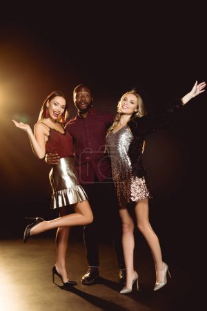 smiling african american man hugging two attractive women while they gesturing by hands on new year party