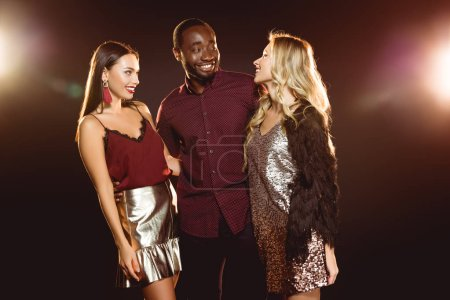 happy african american man hugging two smiling women on new year party
