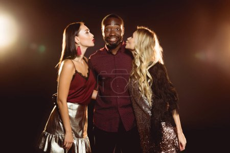 surprised african american man hugging two attractive women while they kissing him in cheeks on new year party