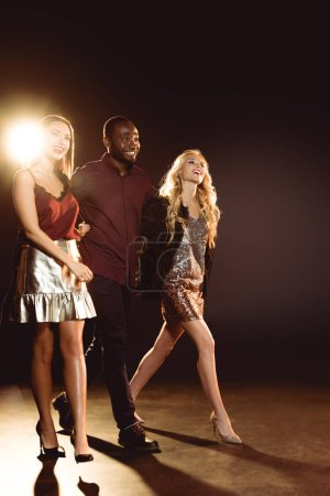 smiling african american man walking and embracing two attractive women on new year party