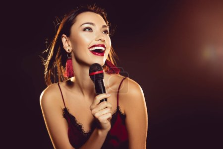 portrait of happy young woman with microphone in hand singing karaoke