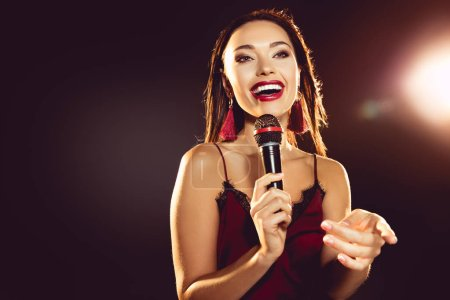 portrait of excited beautiful woman with microphone in hand singing karaoke