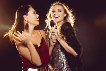 smiling attractive women dancing and singing with microphone in karaoke
