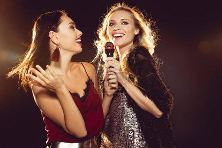 Photo pour Sourire des femmes attirantes dansant et chantant avec microphone karaoke - image libre de droit