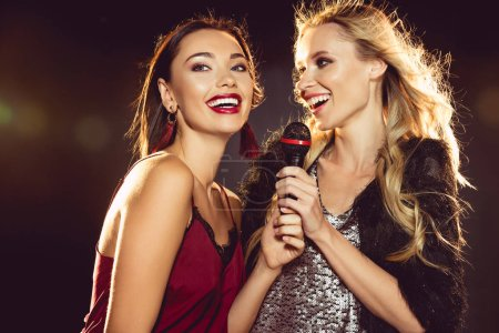 happy beautiful women singing with microphone in karaoke