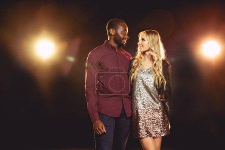 Photo pour Souriant couple multiculturel regardent sur fond noir avec rétro-éclairé - image libre de droit