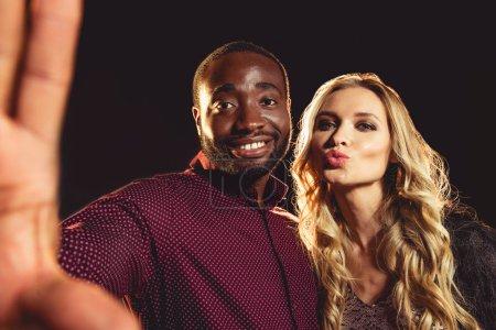 Joyeux couple interracial prenant selfie sur la fête du nouvel an avec rétro-éclairé