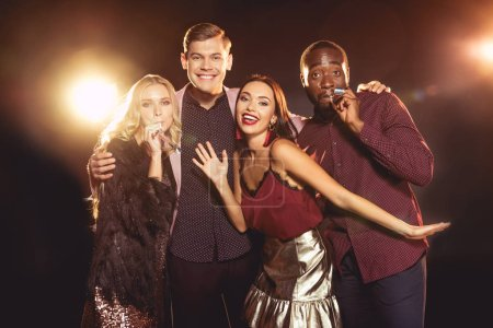 luxury multiethnic friends celebrating new year with party horns on black with backlit