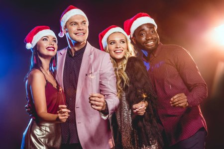 smiling multiethnic friends in santa hats celebrating new year with bengal lights