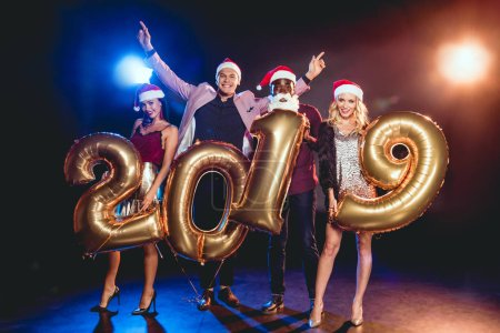multiethnic friends in santa hats holding 2019 new year golden balloons on black with backlit