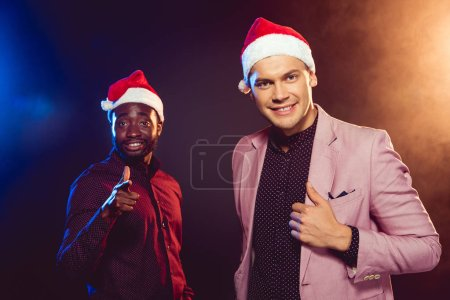 african american man in santa hat pointing at camera while his friend in pink jacket posing on black with backlit