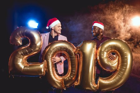 multicultural friends in santa hats looking at each other while holding 2019 new year golden balloons on smoke and backlit