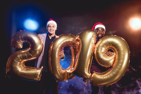cheerful multiethnic friends in santa hats holding 2019 new year golden balloons on smoke and backlit
