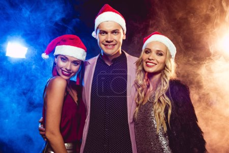 smiling man in pink jacket embracing two women in santa hats on smoke with backlit