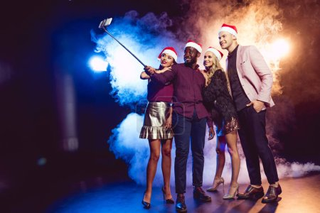 Photo for Multiethnic friends in santa hats taking selfie on smartphone on new year party with smoke - Royalty Free Image