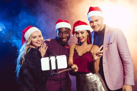 happy multicultural friends in santa hats with victory sign taking selfie on smartphone