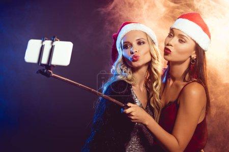 beautiful women in santa hats with kiss grimace taking selfie on smartphone