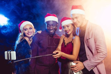 happy multiethnic friends in santa hats taking selfie on smartphone