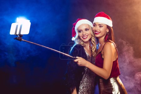 Photo pour Heureuse jolies filles en chapeaux santa prenant selfie sur smartphone - image libre de droit