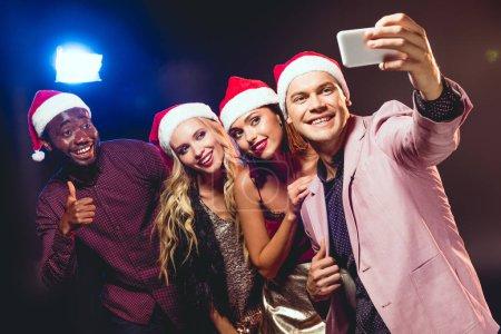 Photo pour Glamours amis multiculturels dans chapeaux santa prenant selfie sur smartphone - image libre de droit