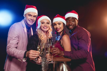 multicultural glamorous friends in santa hats clinking with champagne glasses on new year party