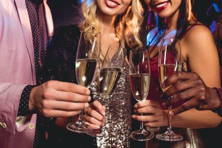 recorta la vista de amigos glamour tintinear con copas de champagne