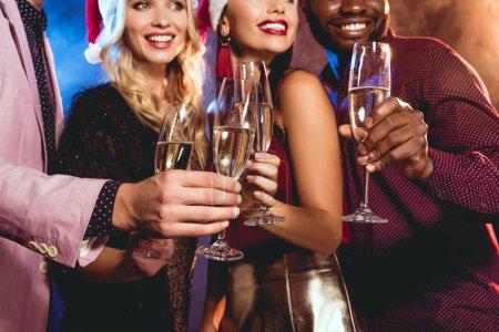 Photo pour Amis multiethniques dans chapeaux santa tinter les verres de champagne sur la fête du nouvel an - image libre de droit