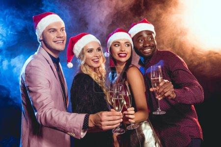 Photo pour Sourire des amis multiethniques dans chapeaux santa tinter les verres de champagne sur la fête du nouvel an - image libre de droit