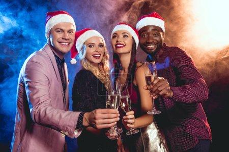 Photo pour Peuple multiethnique luxe en chapeaux santa tinter les verres de champagne sur la fête du nouvel an - image libre de droit