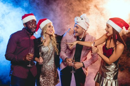 excited multicultural friends in santa hats with champagne glasses on new year party