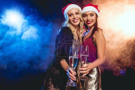 Photo pour Jolies filles souriantes en chapeaux santa grillage avec des verres de champagne sur new year party - image libre de droit