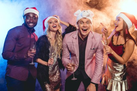 excited multiethnic friends in santa hats celebrating new year with champagne glasses on party