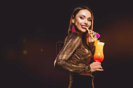 beautiful glamorous girl drinking alcohol cocktail on black