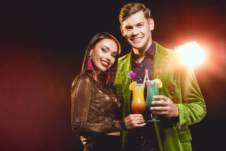 beautiful glamorous couple clinking with cocktail glasses on party with back light